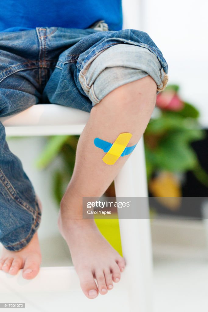 Child knee with an adhesive bandage : Stock Photo