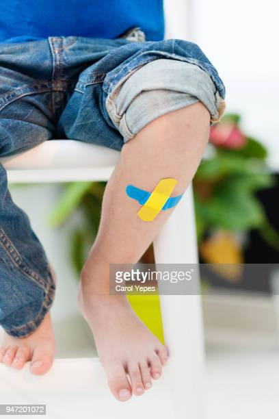 child knee with an adhesive bandage - bruise stock photos and pictures
