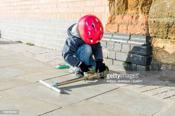 Child Kneeling On Footpath Wearing Red Helmet Repairing Scooter By Wall