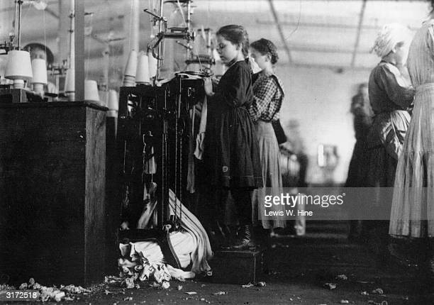 A child laborer stands on a wooden stool in order to reach her knitting machine as she makes stockings in a textile factory
