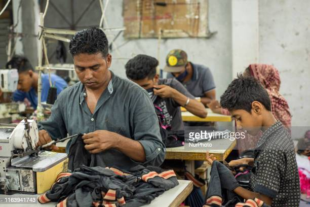 Child labour working with his adult co-workers in a local ready made garments factory at Narayanganj, Bangladesh on August 25, 2019.
