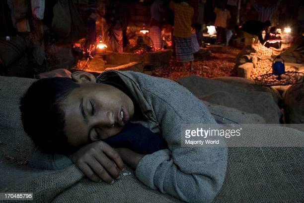 A child labourer sleeps on jute sacks at a wholesale market in Dhaka city in Bangladesh February 28 2008