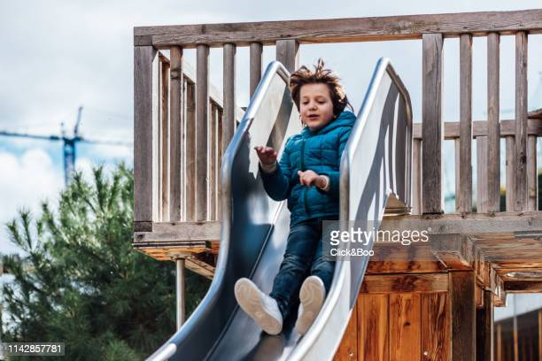 child laughting on a slide outdoors - click&boo fotografías e imágenes de stock