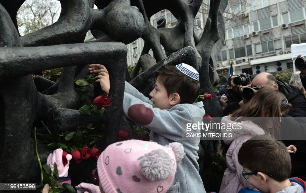 Child lay roses at the Holocaust Memorial monument downtown Thessaloniki on January 26 during the International Holocaust Remembrance Day which...