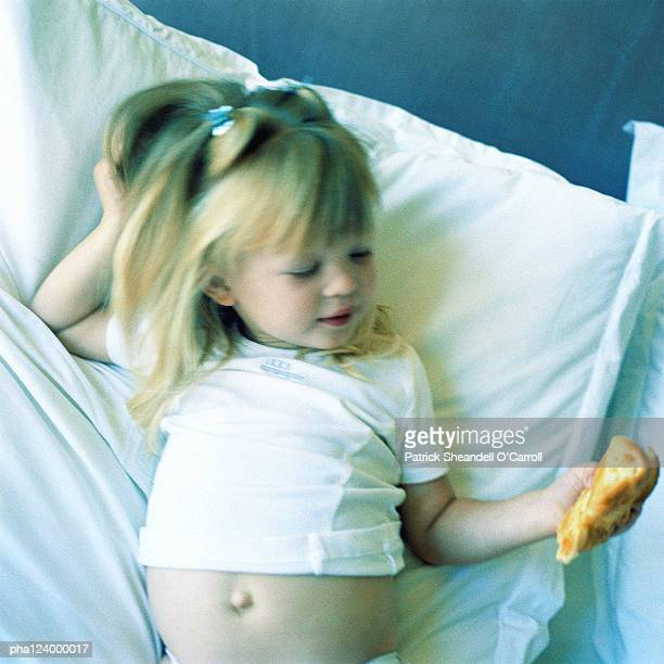 Child laying on bed, holding food