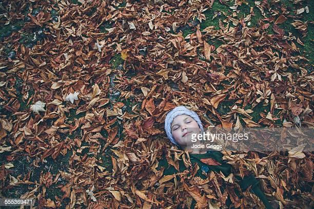 child laying on ground surrounded by autumn leaves - grande gruppo di oggetti foto e immagini stock