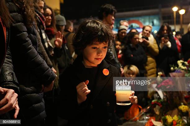 A child lays a candle next to a mural of David Bowie in Brixton on January 11 2016 in London England British music and fashion icon David Bowie died...