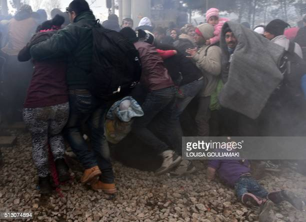 TOPSHOT A child lays on the ground as migrants and refugees run away after Macedonian police fired tear gas at hundreds of Iraqi and Syrian migrants...