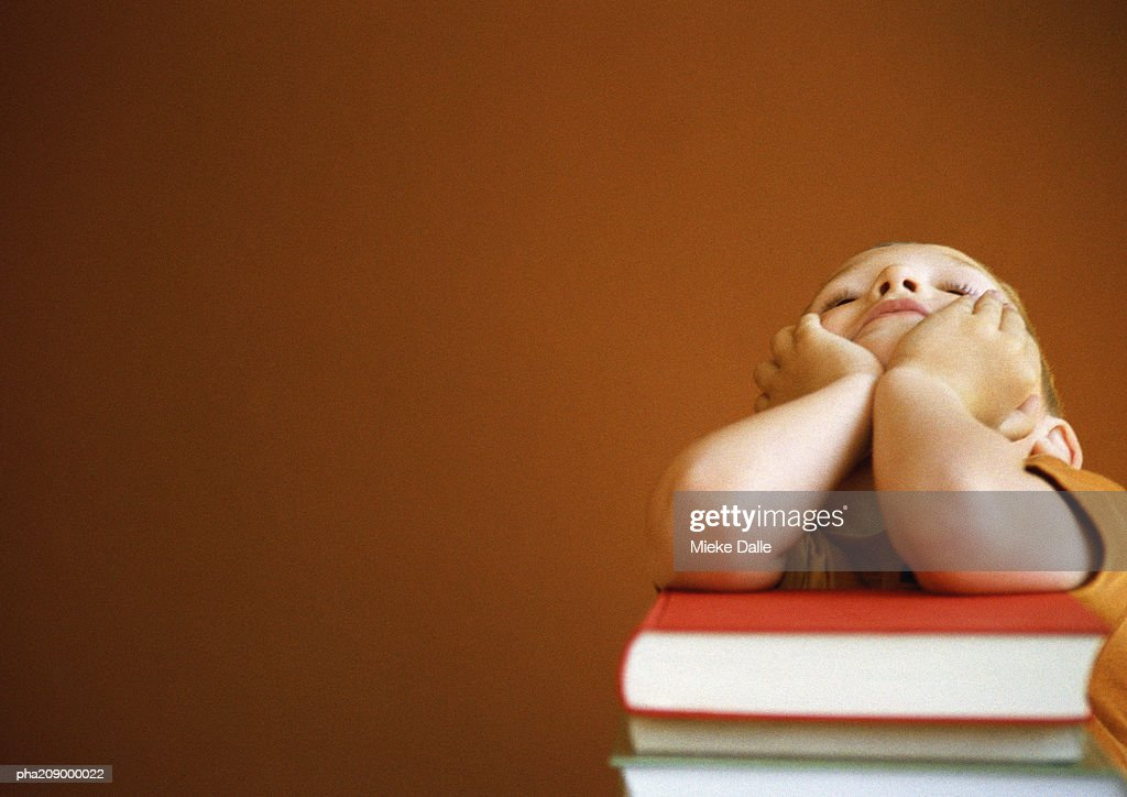 Child leaning on books, head in hands, portrait. : Stockfoto