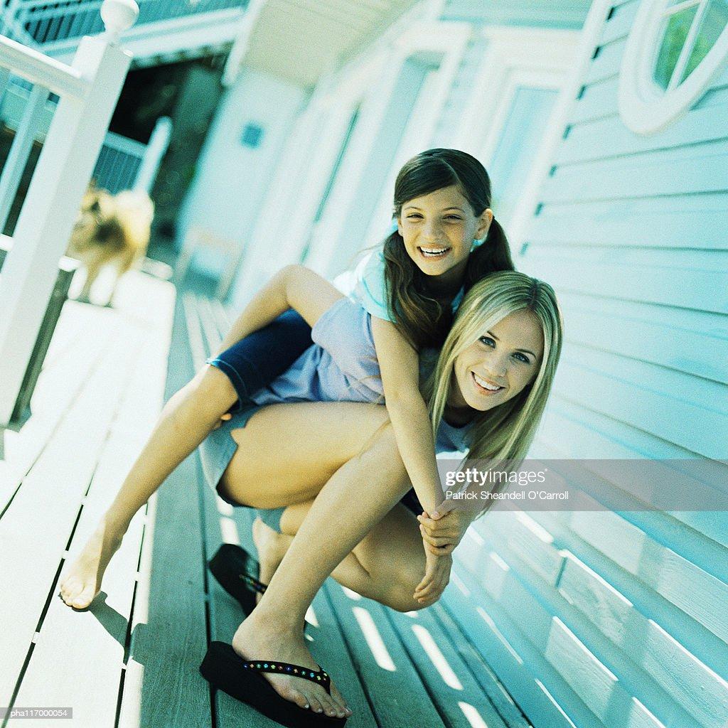 Child leaning on teenage girl's back : Stockfoto