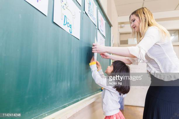 child learning english language while playing games in classroom - english language stock pictures, royalty-free photos & images