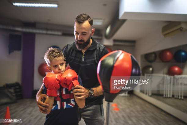 Child learning guard in boxing from a personal trainer