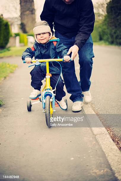 Child learning to ride bicycle
