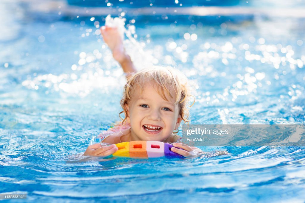 Child learning to swim. Kids in swimming pool. : Stock Photo