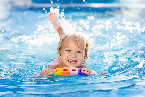 Child learning to swim. Kids in swimming pool. 1132353492