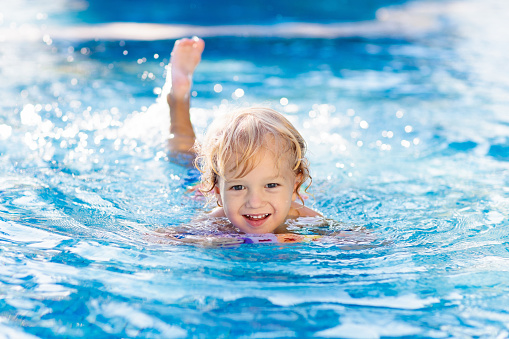 Child learning to swim. Kids in swimming pool. 1150164812