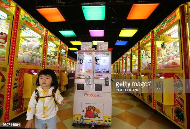 A child leaves from a claw machine shop in Taipei on March 12 2018 / AFP PHOTO / Pichi Chuang