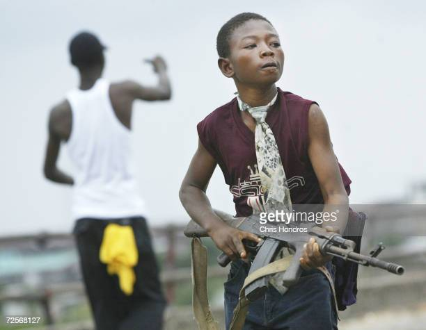 Child Liberian militia soldier loyal to the government walks away from firing while another taunts them on July 30, 2003 in Monrovia, Liberia....