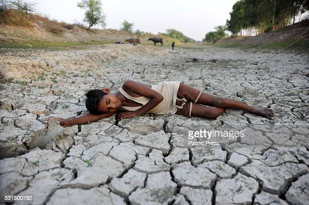 A child lies down on a dry bed of parched mud that is the dried up River Varuna at Phoolpur Much of India is reeling from a heat wave and severe...