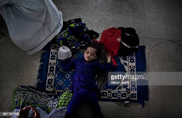 A child lies on a prayer rug at Baitul Mukarram the National Mosque on Eid AlFitr July 18 2015 in Dhaka Bangladesh Muslims around the world are...