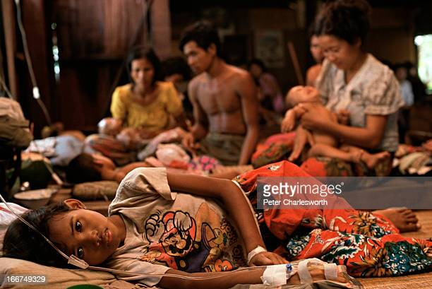 A child lies on mats as parents care for othe children and babies in a one room wooden hospital run by the International Red Cross Most of the...