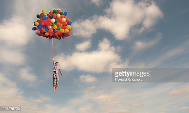 child lifted into sky by huge bunch of balloons