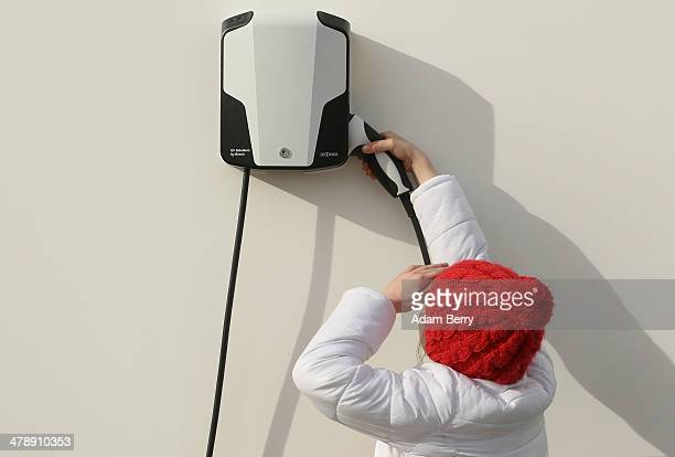 Child lifts the handle of an electric automobile charger at the Electric Mobility Week , a public Volkswagen event at the former Tempelhof airport,...