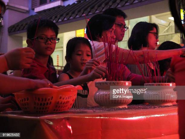 CHINATOWN MANILA PHILIPPINES A child lighting an insense with family during the chinese new year celebration Filipinos celebrated the Chinese New...