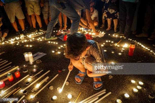 A child lights a candle during the vigil service People gathered outside the Hellenic Parliament in memory of the 91 victims of the deadly fire in...