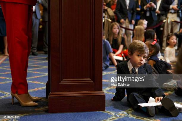 A child listens to House Minority Leader Nancy Pelosi speak with journalists' kids during her weekly press conference on 'Take our Daughters and Sons...