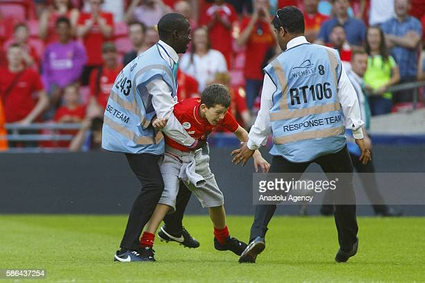 A child Liverpool fan intrudes into the pitch after an International Champions Cup match between Liverpool FC and FC Barcelona at Wembley Stadium on...