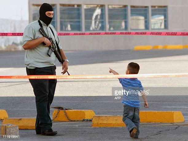 A child look to the Ministerial Police stand next to truck with two bodies killed in Ciudad Juarez Mexico on April 08 2011 An estimated 35000 people...