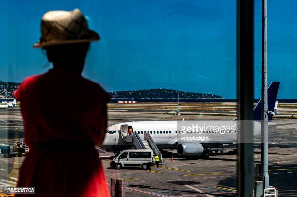 child (7-8) looking at a parked airplane. - red dress stock pictures, royalty-free photos & images