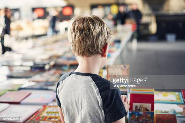 child looking at books - book store stock photos and pictures