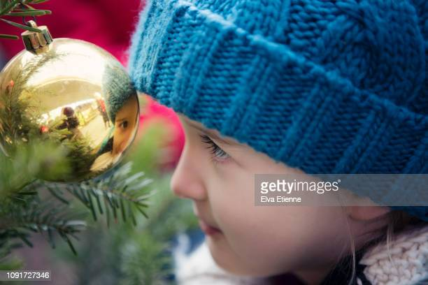 Child (6-7) looking at her own reflection in a shiny Christmas bauble on a fir tree