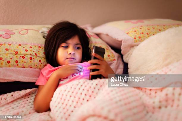 Child Looking at Phone in Her Bed