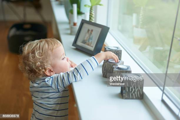 Child looking at some candle lights in the window