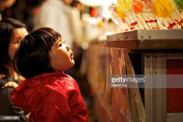 child looking at toffee fruit candy - shinto shrine stock pictures, royalty-free photos & images
