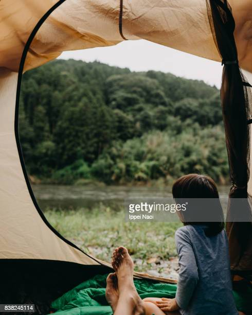 Child looking at view from camping tent in morning