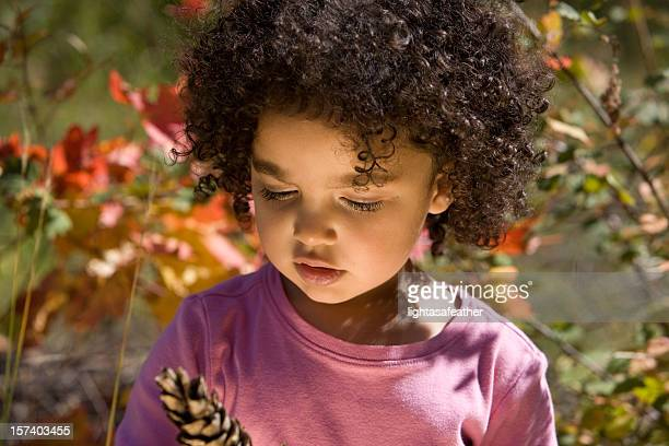 Child Looking Intently at a Pine Cone