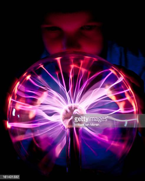 Child looking into the electric glow from a plasma globe. Science, energy, fasination