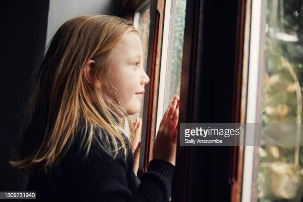 child looking out of a window - sally anscombe stock pictures, royalty-free photos & images