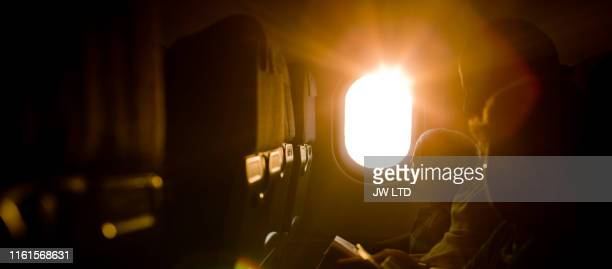 child looking out of airplane window - airplane stock pictures, royalty-free photos & images