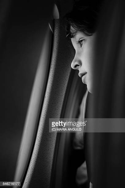A child looking out of the window of an airplane