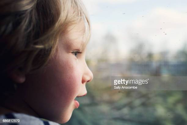 child looking out of the window on a train - menino loiro olhos azuis imagens e fotografias de stock