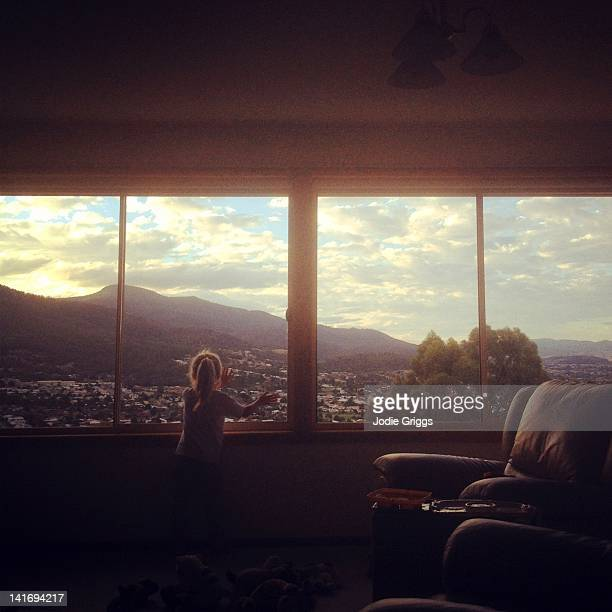 child looking out of window - town stock pictures, royalty-free photos & images