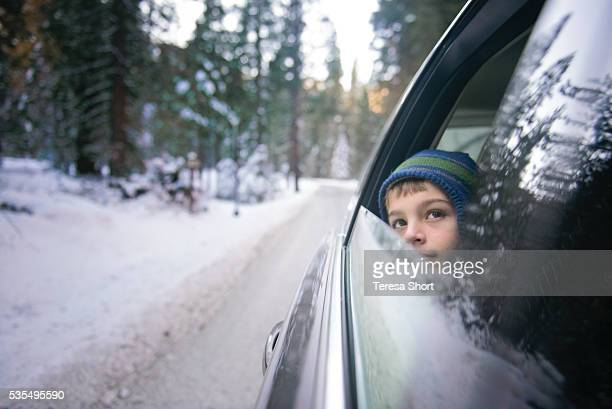 Child looking out open car window while driving through snow