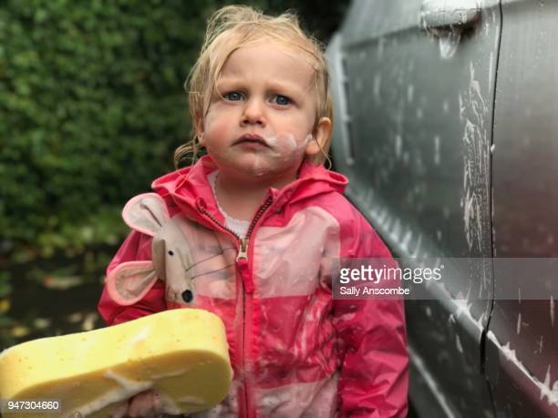 Child looking past camera holding a sponge