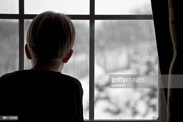 Child Looking Though Window at Snow