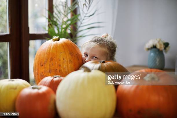 Child looking through a pile of pumpkins